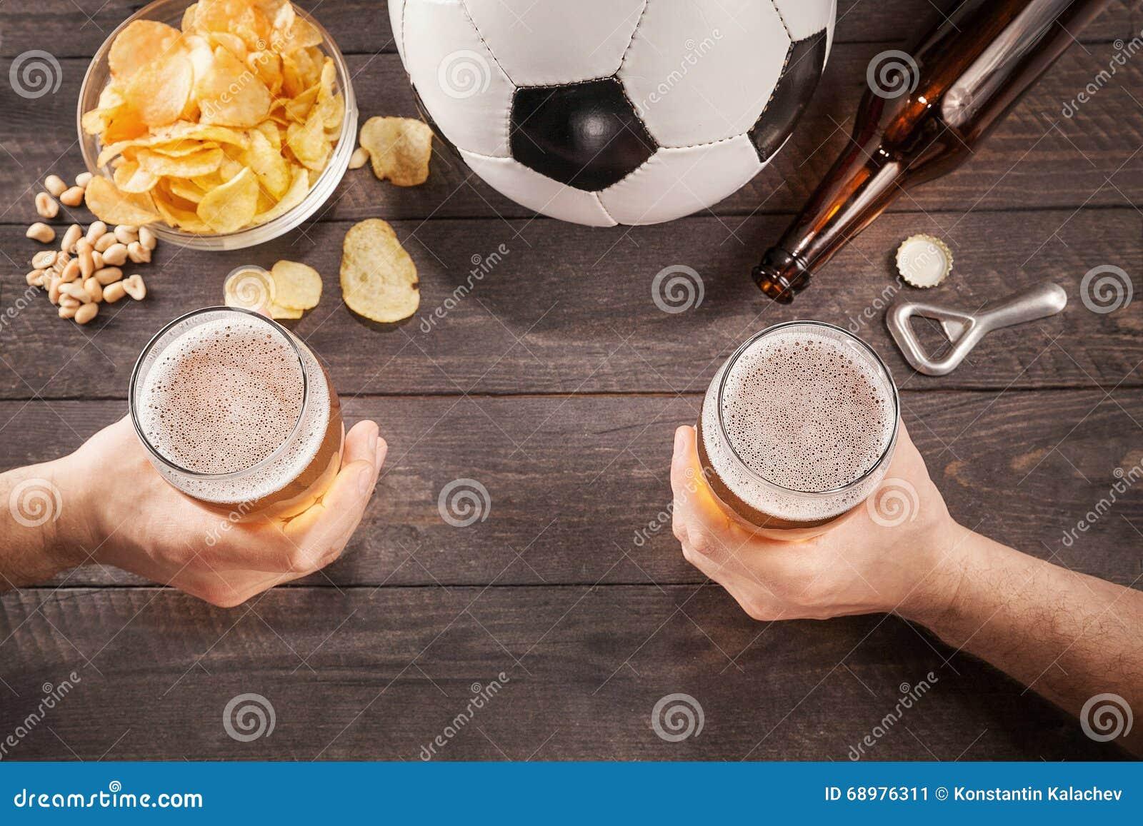 Dos vidrios de cerveza en las manos de los hombres Chin-Chin