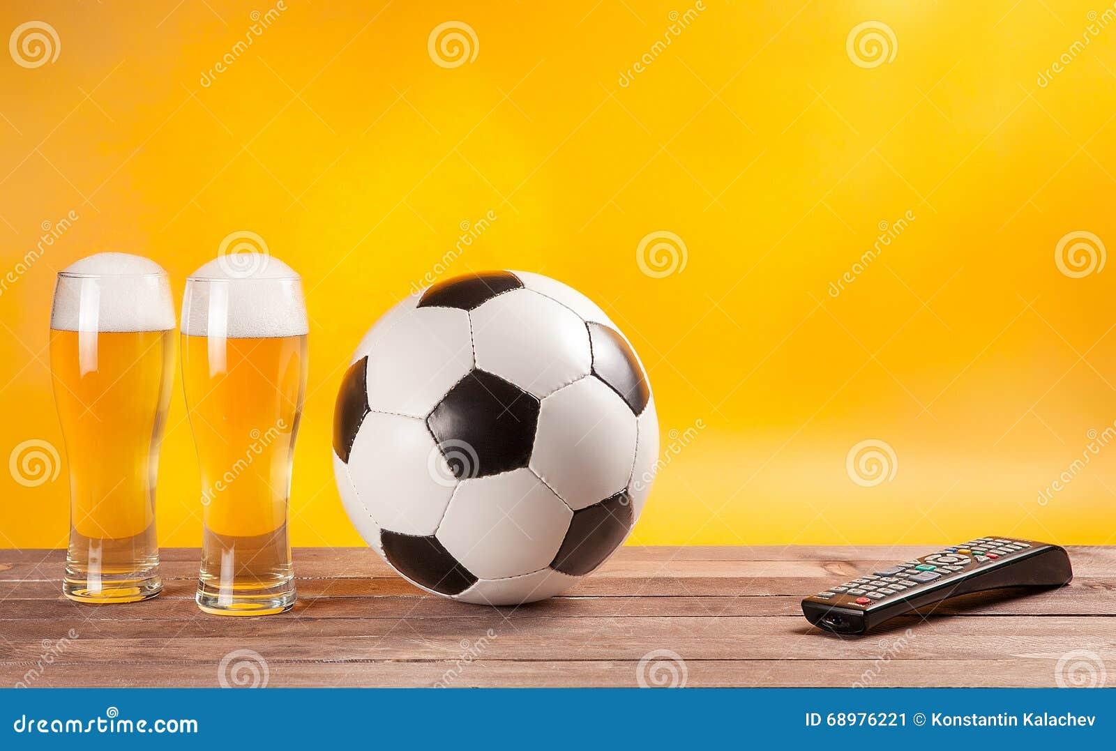 Dos vidrios de la cerveza y balón de fútbol cerca del telecontrol de la TV