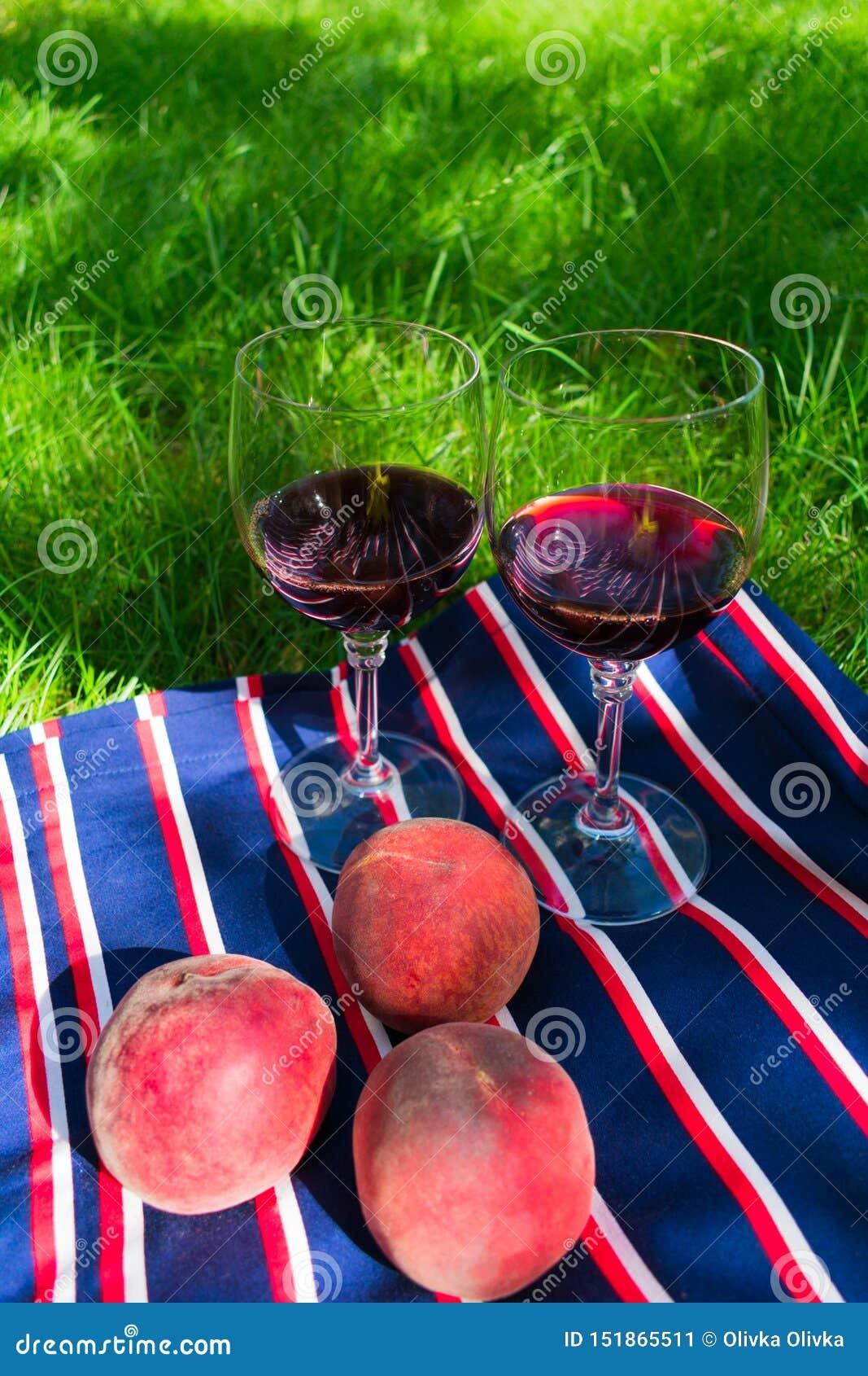 Dos vidrios de vino tinto, en un fondo de la hierba El concepto de una comida campestre romántica en naturaleza