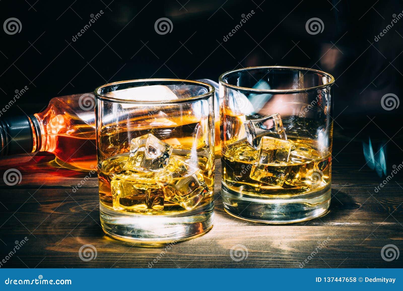 Dos vidrios del whisky escocés o del coñac con los cubos de hielo y la botella de licor del alcohol en fondo de madera oscuro