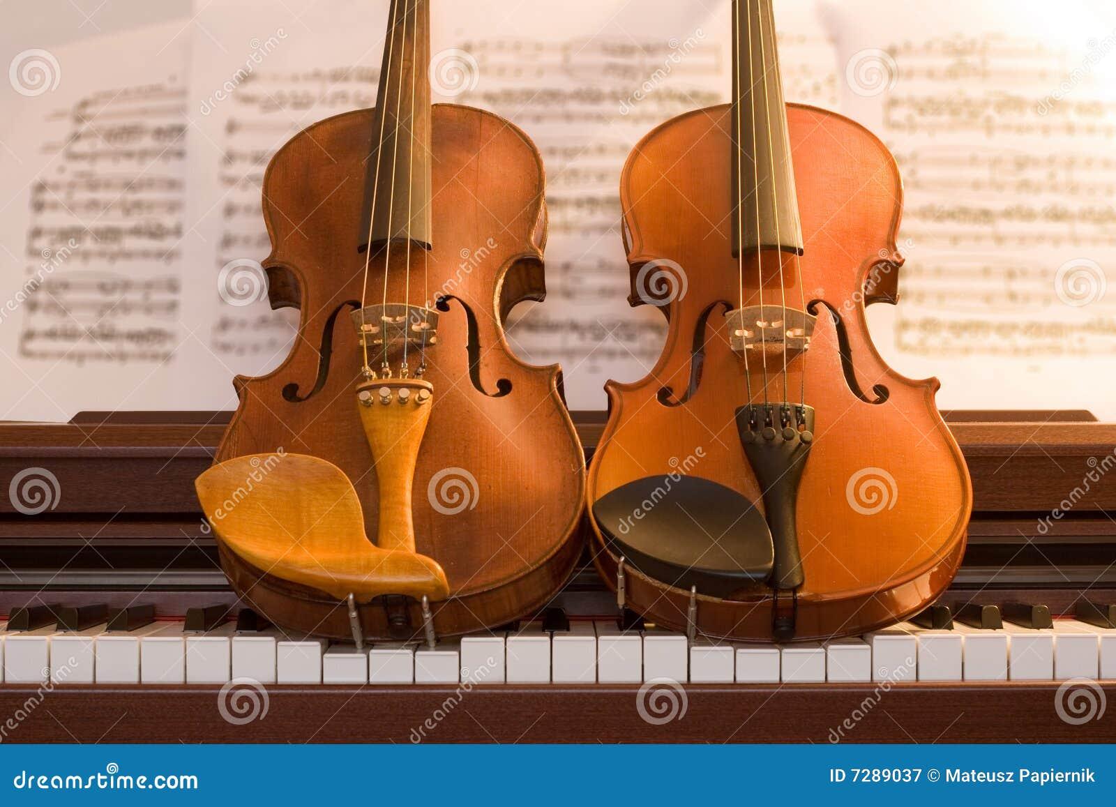 Dos violines encima de claves del piano