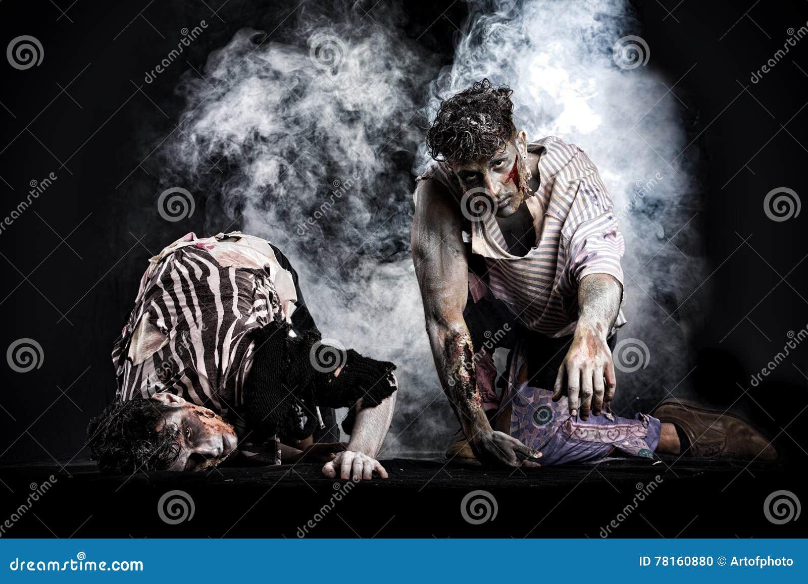 Dos zombis masculinos que se arrastran en sus rodillas, en fondo ahumado negro
