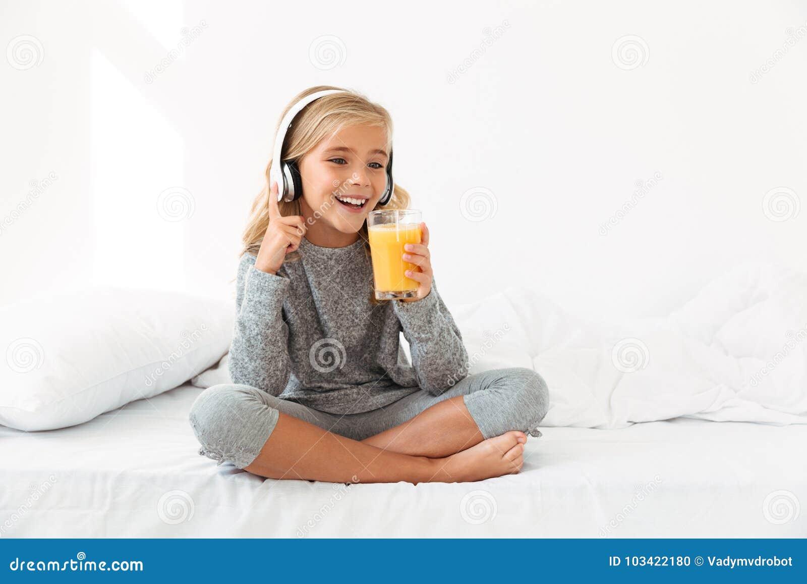 Dosyć mała blondynki dziewczyna trzyma szkło orang w szarych piżamach
