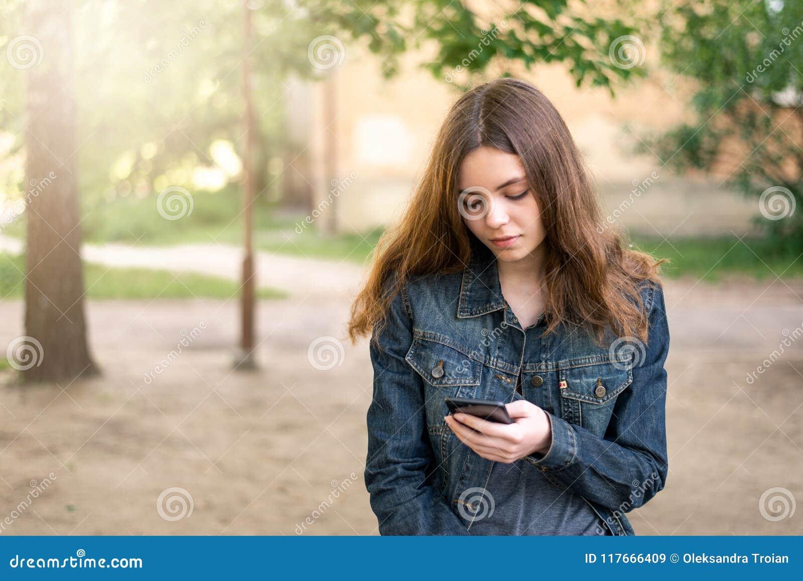 Dosyć nastoletnia dziewczyna używa telefon w ogólnospołecznych środkach