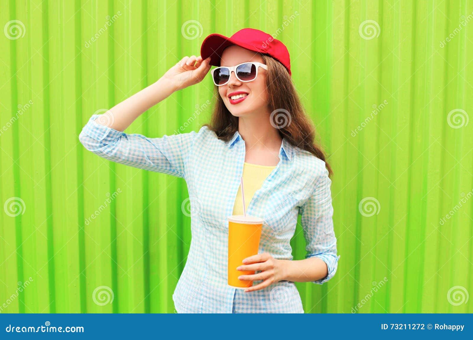 Dosyć uśmiechać się kobiety w okularach przeciwsłonecznych z filiżanką owocowy sok nad kolorową zielenią