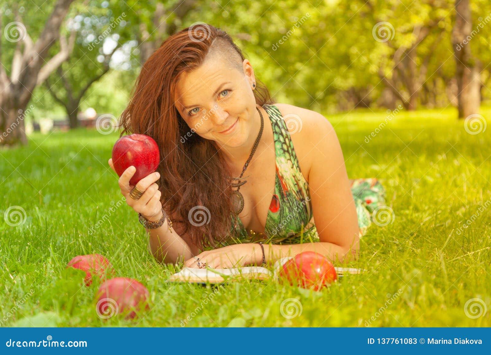 Dosyć uśmiechać się szczęśliwej dziewczyny w zieleni sukni czytelniczej książce i lying on the beach na trawie