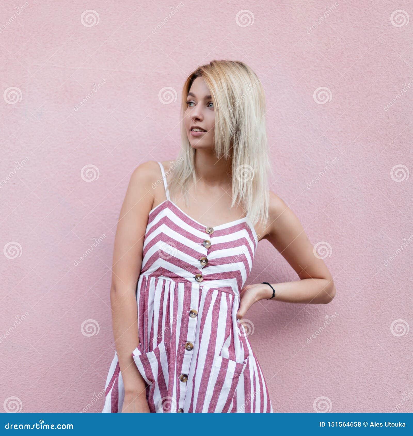 Dosyć wspaniała młoda kobieta z ślicznym uśmiechem z blondynem w modnych pasiastych menchii smokingowy pozuje stać