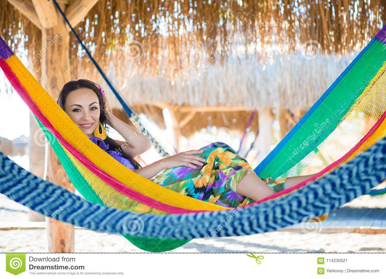 Dosyć zdziwiona rozochocona młoda dziewczyna na plaży, ono uśmiecha się kłama w hamaku przeciw tłu drzewka palmowe, styl życia, g