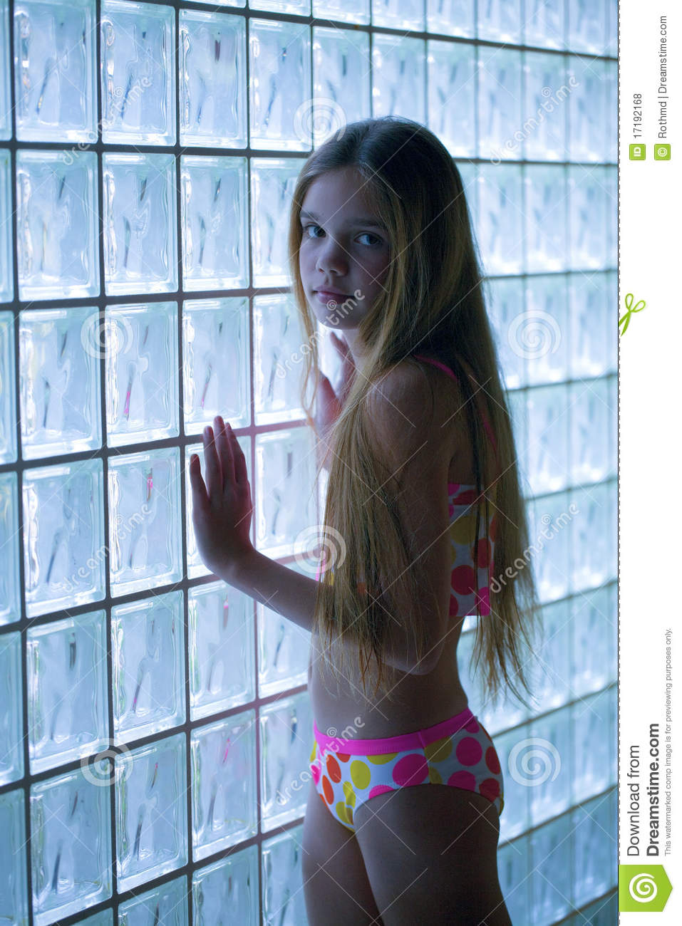 young girl stands by a glass wall wearing a bikini.