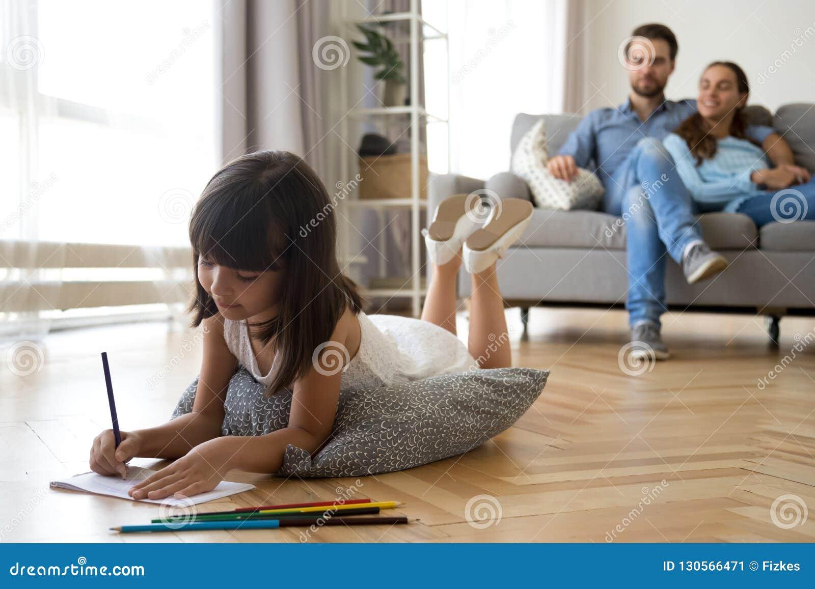 Dotterattraktioner som ligger på varma golvföräldrar som sitter på soffan