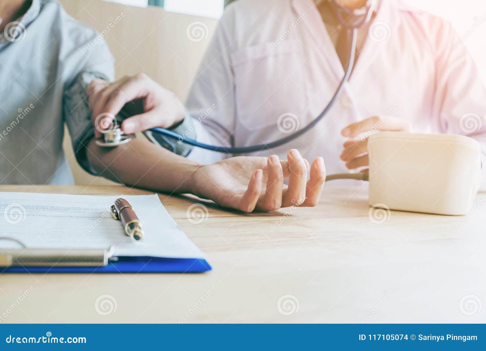 Dottore il paziente arterioso della donna di pressione sanguigna di Measuring sulla destra