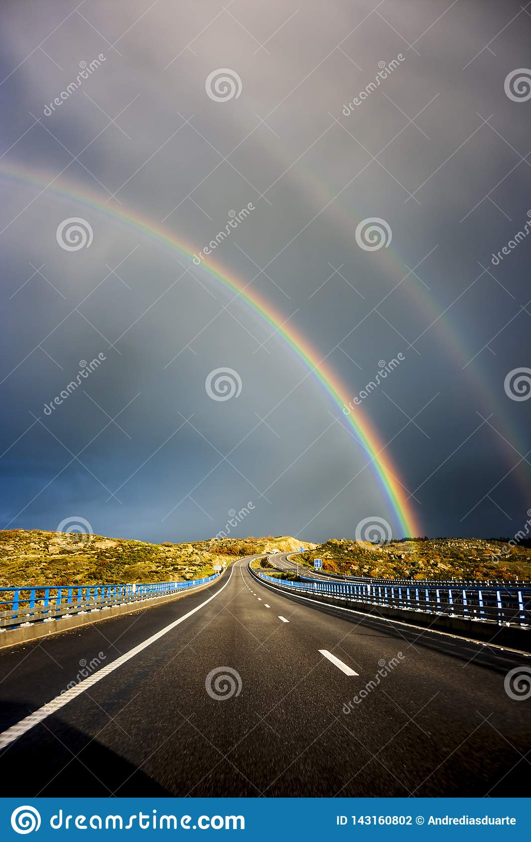 Double arc-en-ciel au-dessus de la route
