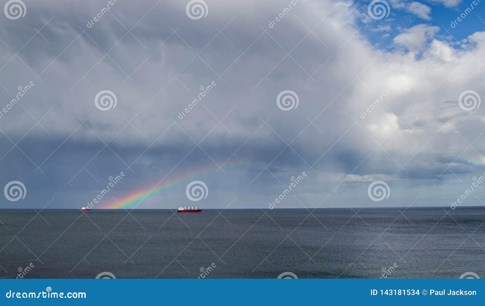 Double arc-en-ciel en mer au-dessus de quelques bateaux