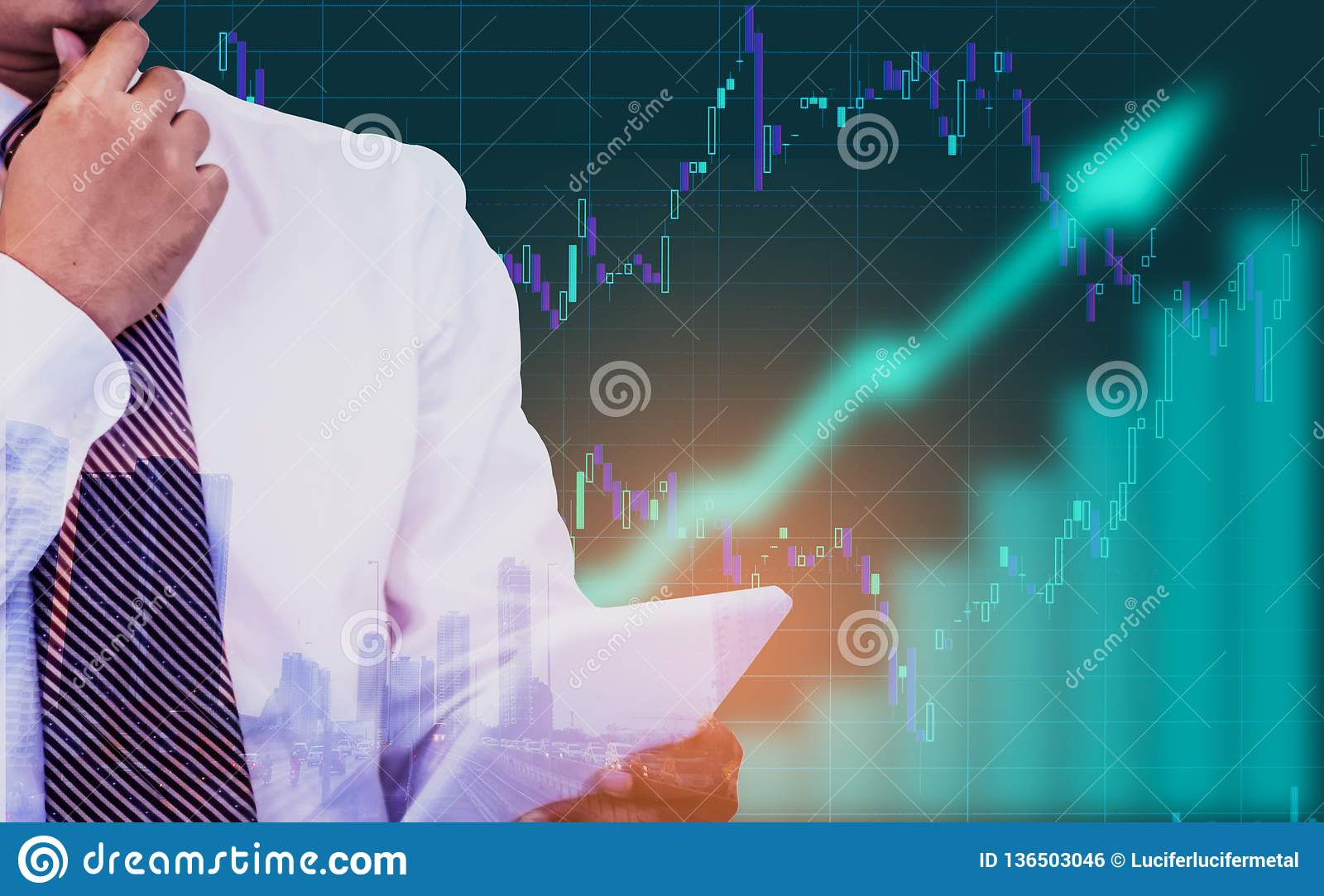 Double exposure - businessman holding a tablet in hand, background is an arrow sign and stock graphs and icons,Concept of