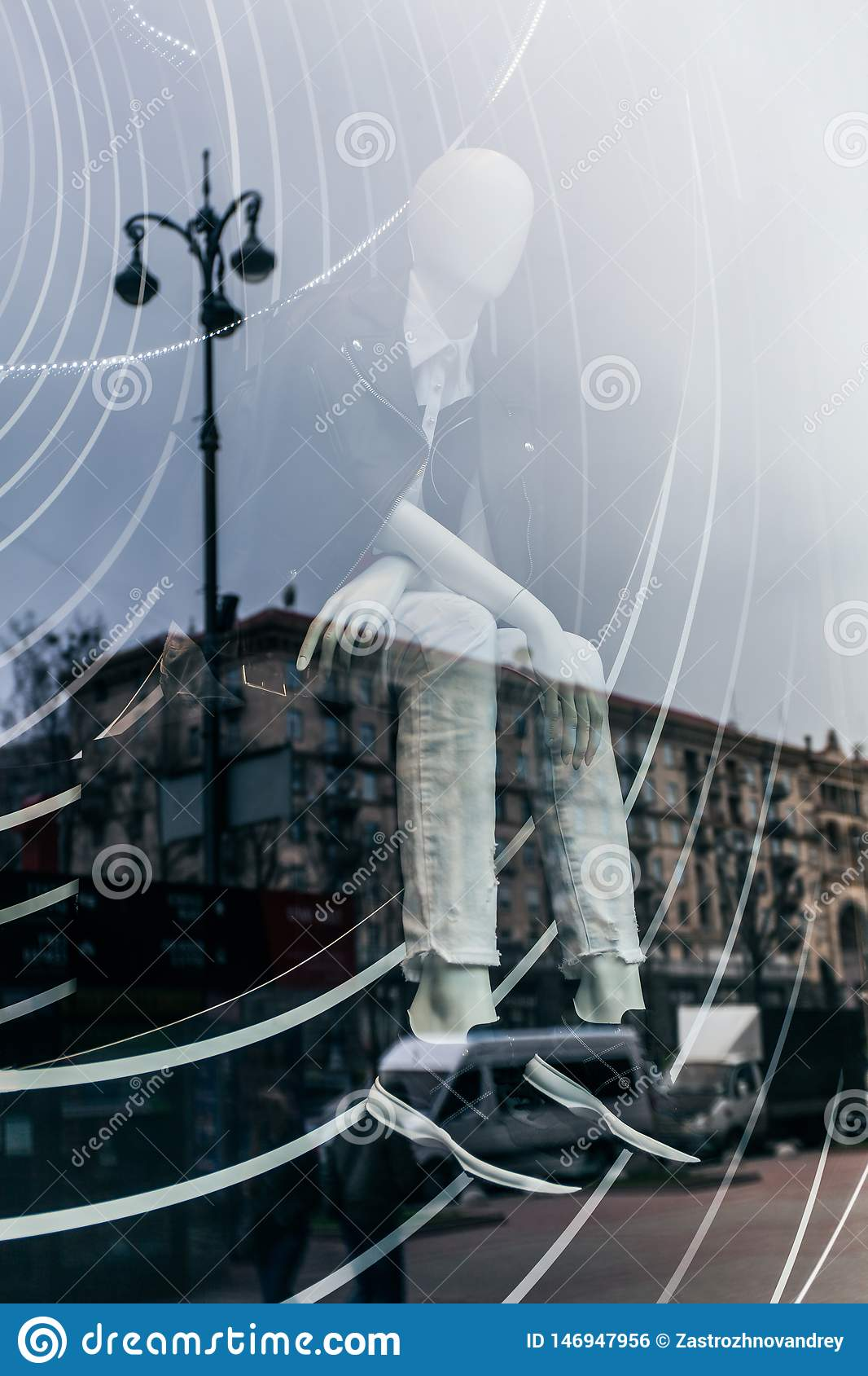 Double exposure is a reflection of the city on the glass shop window with a mannequin in fashionable clothes