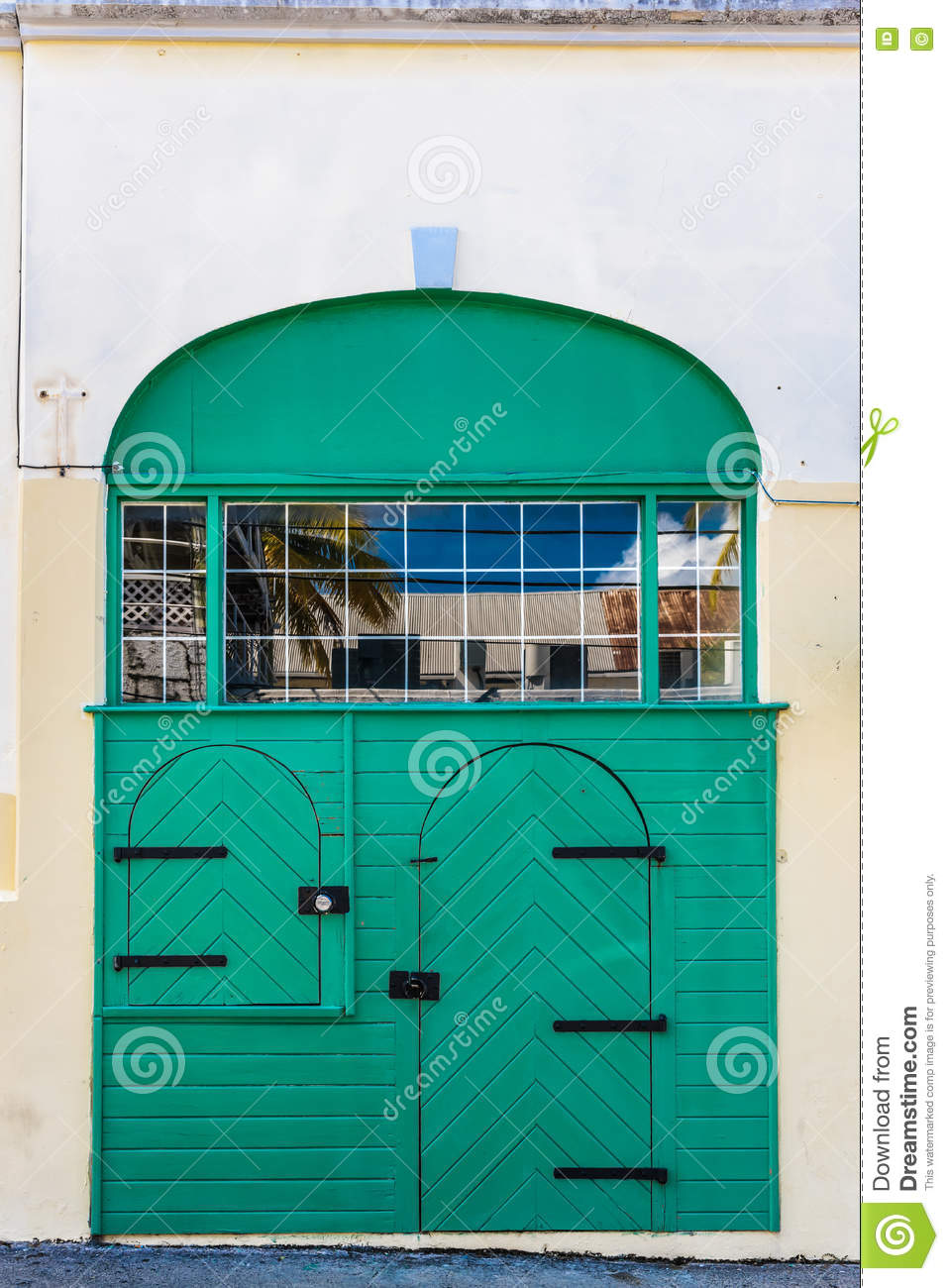 Double green door with archways and window reflection