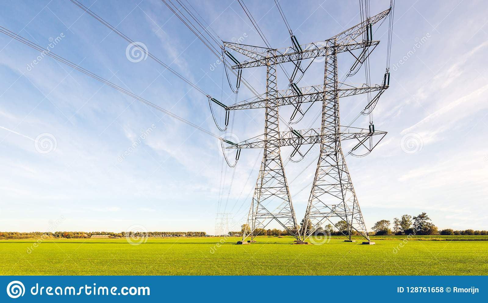 Double rangée des lignes électriques et des pylônes dans une terre rurale néerlandaise plate
