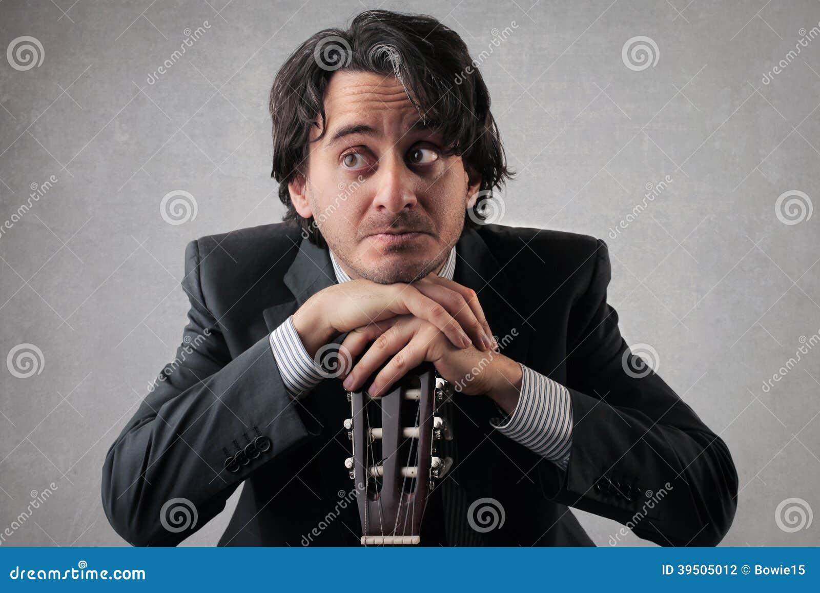 Doubtful businessan with a guitar