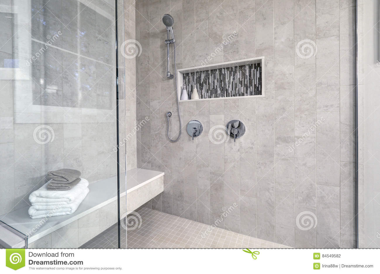 Douche de plain-pied en verre dans une salle de bains maison de toute neuve