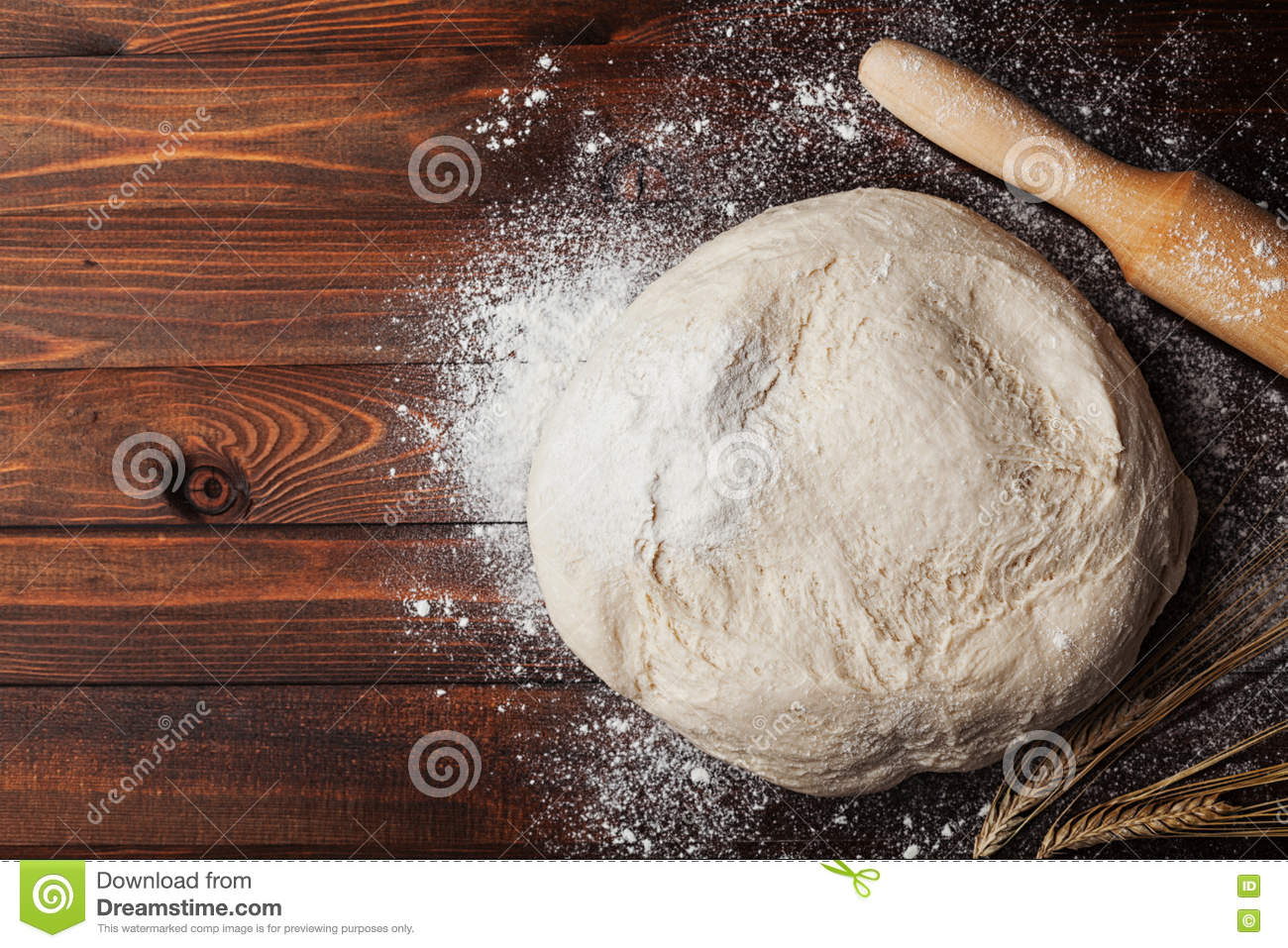 Dough with flour, rolling pin, wheat ears on rustic wooden table from above. Homemade pastry for bread or pizza. Bakery background