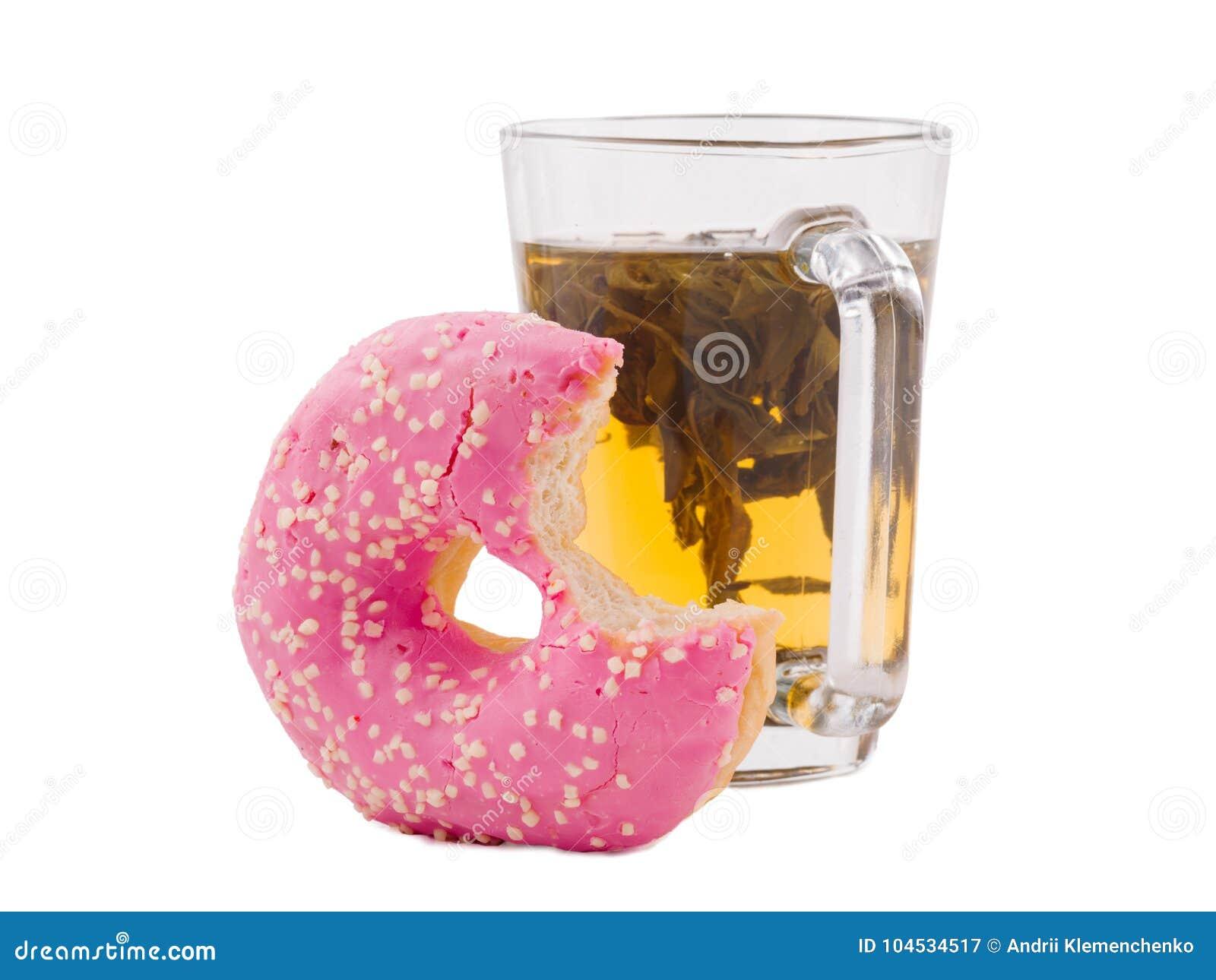 Doughnut die met een kop thee op een wit geïsoleerde achtergrond wordt gebeten