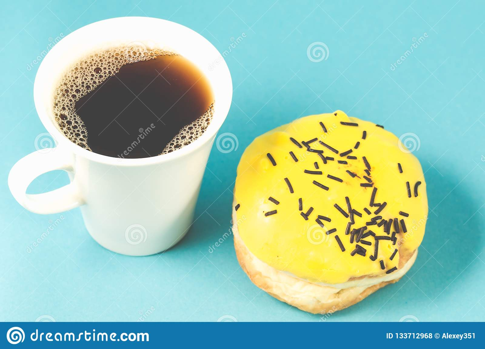Doughnut en coffe kop op blauwe achtergrond/Doughnut die in geel wordt geïsoleerd