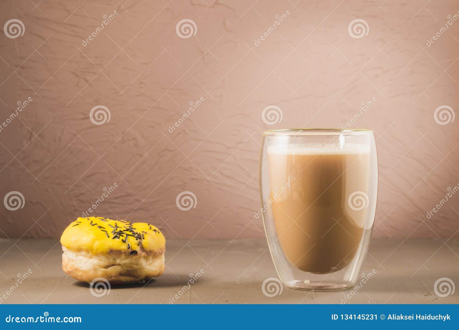 Doughnut in gele glans en een cappuccinoglas /donut in gele glans en een cappuccinoglas op een bruine achtergrond Selectieve nadr