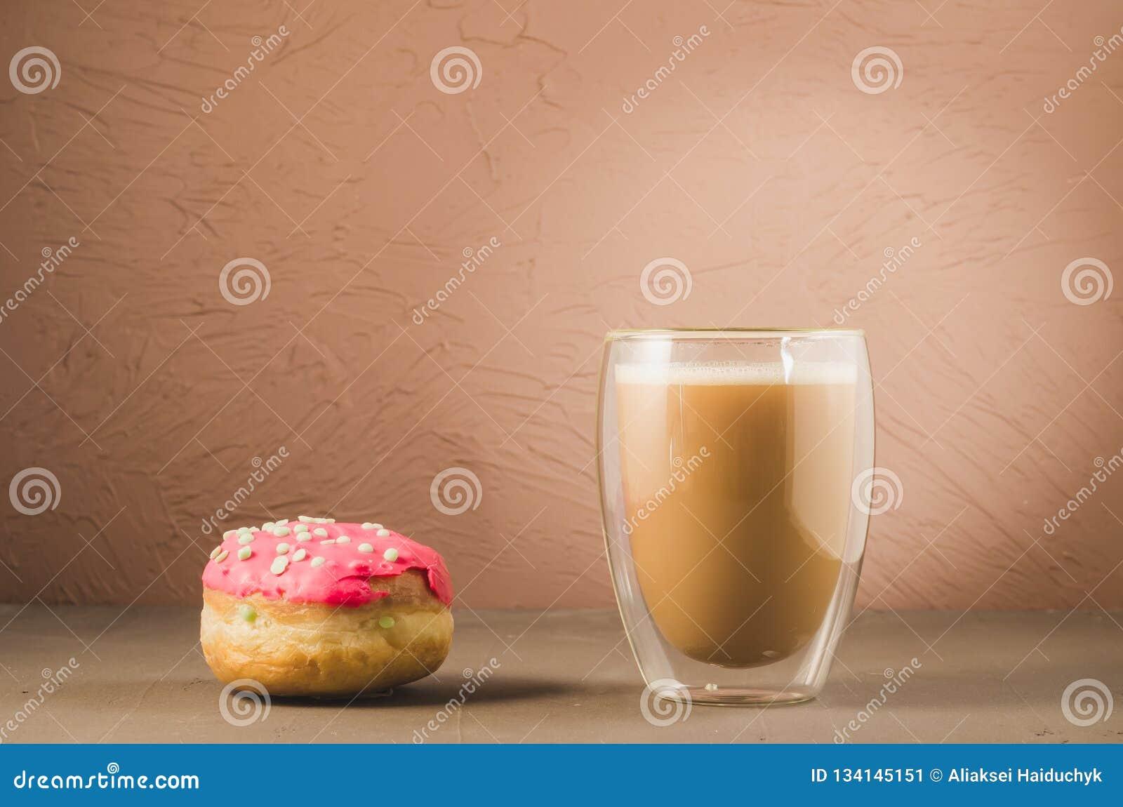 Doughnut in rode glans en een cappuccino /donut in rood glans en cappuccinoglas op een bruine achtergrond