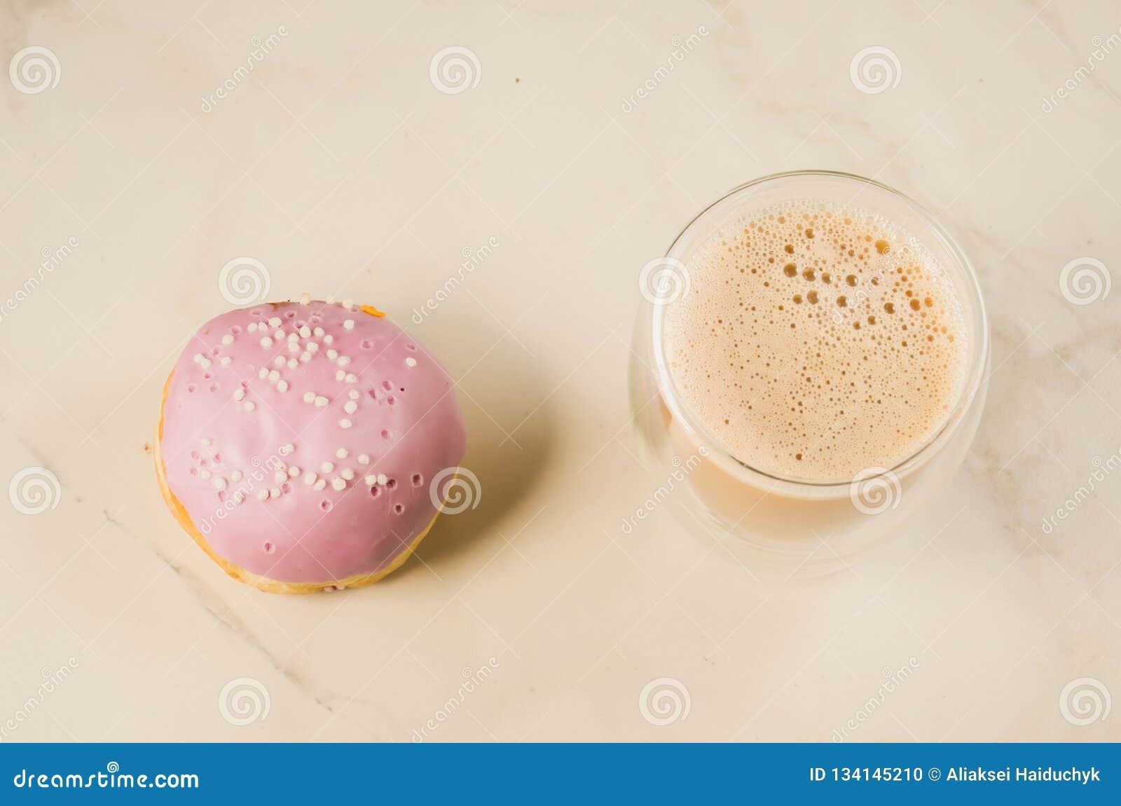 Doughnut in violette glans en een cappuccinoglas /donut in violette glans en een cappuccinoglas op een witte achtergrond, hoogste
