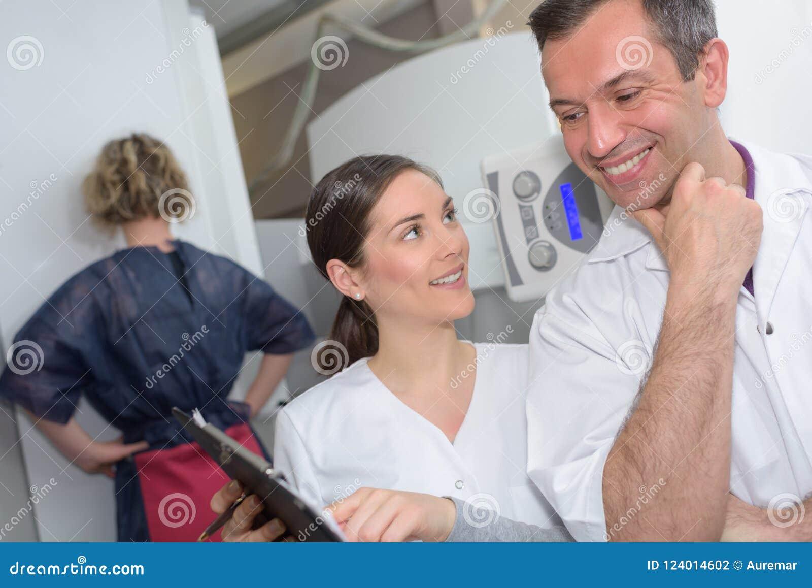 Doutor alegre e assistente masculinos que guardam a tabuleta digital ao rir