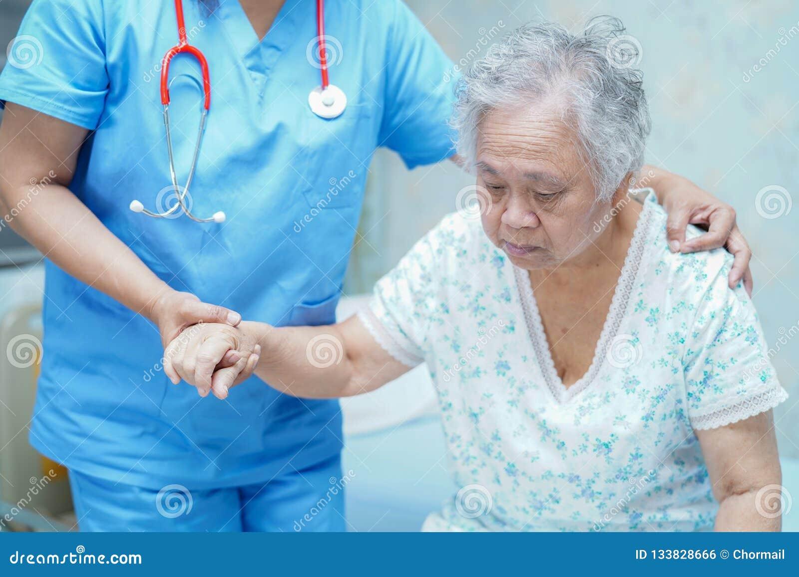 Doutor asiático do fisioterapeuta da enfermeira para importar-se, ajudar e apoiar o paciente idoso da mulher da senhora idosa
