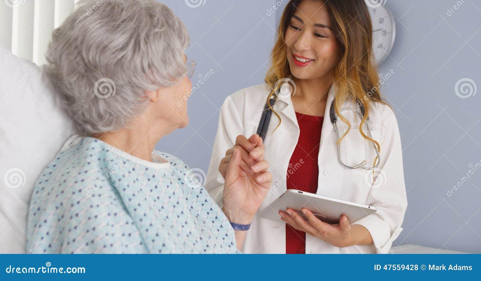 Doutor asiático que guarda a mão do paciente idoso da mulher no hospital