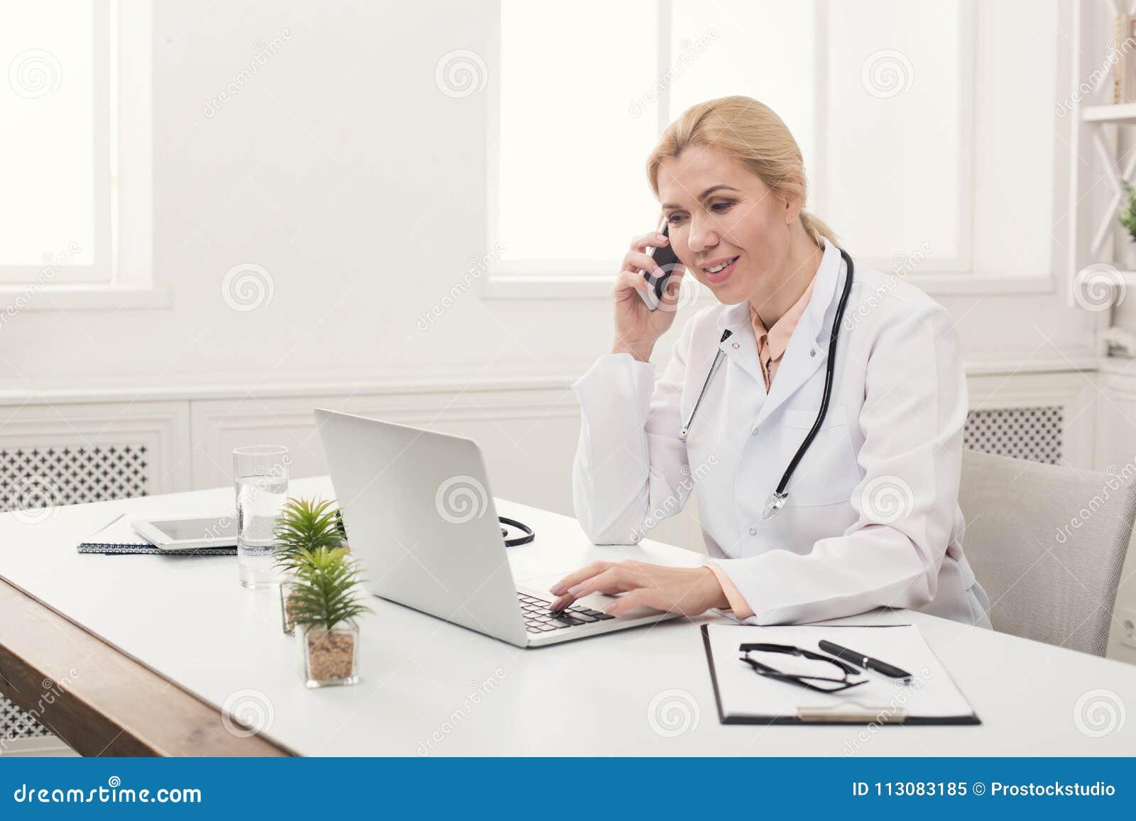 Doutor atrativo que fala no telefone com paciente