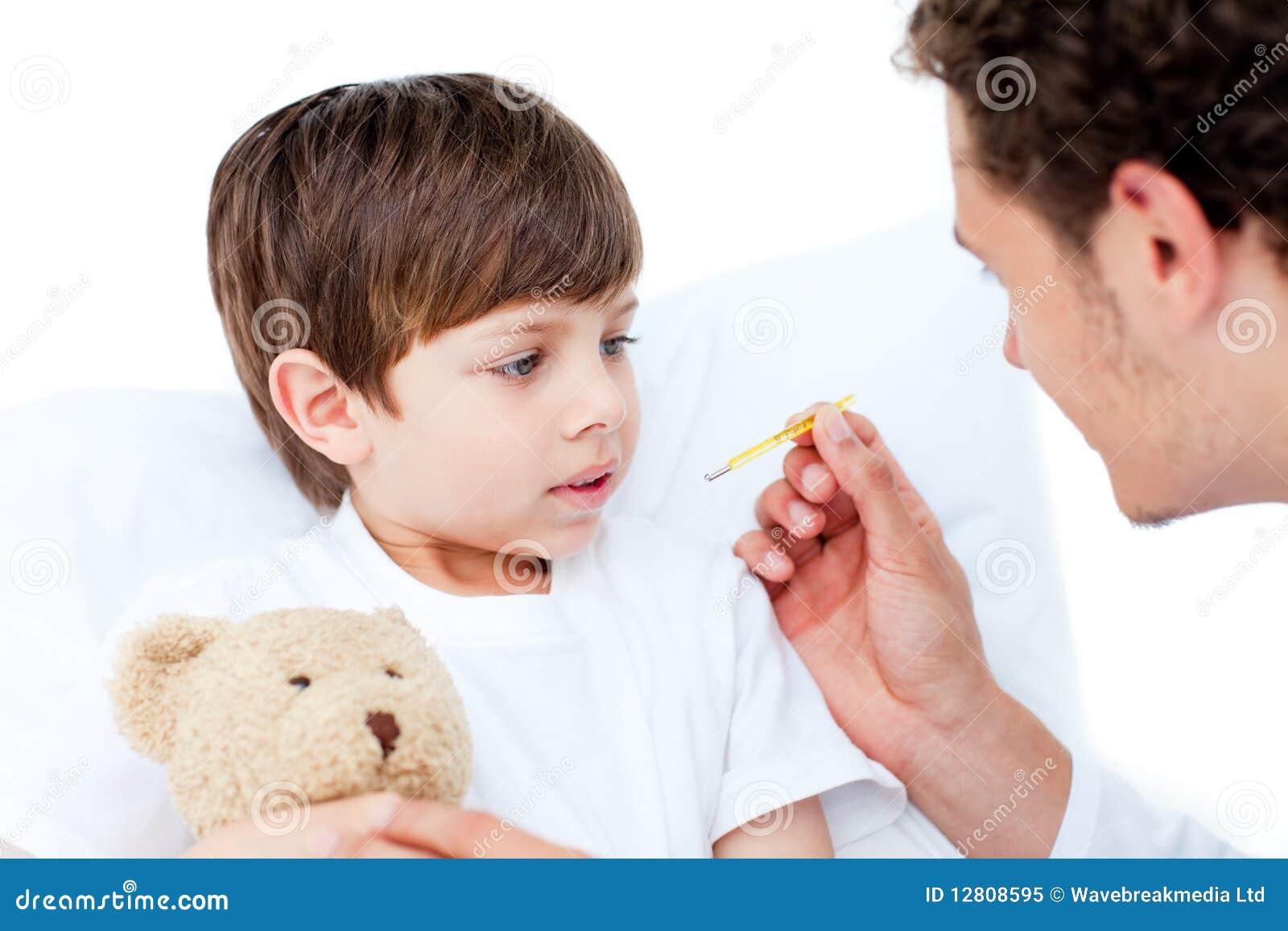 Doutor caucasiano que toma a temperatura do rapaz pequeno