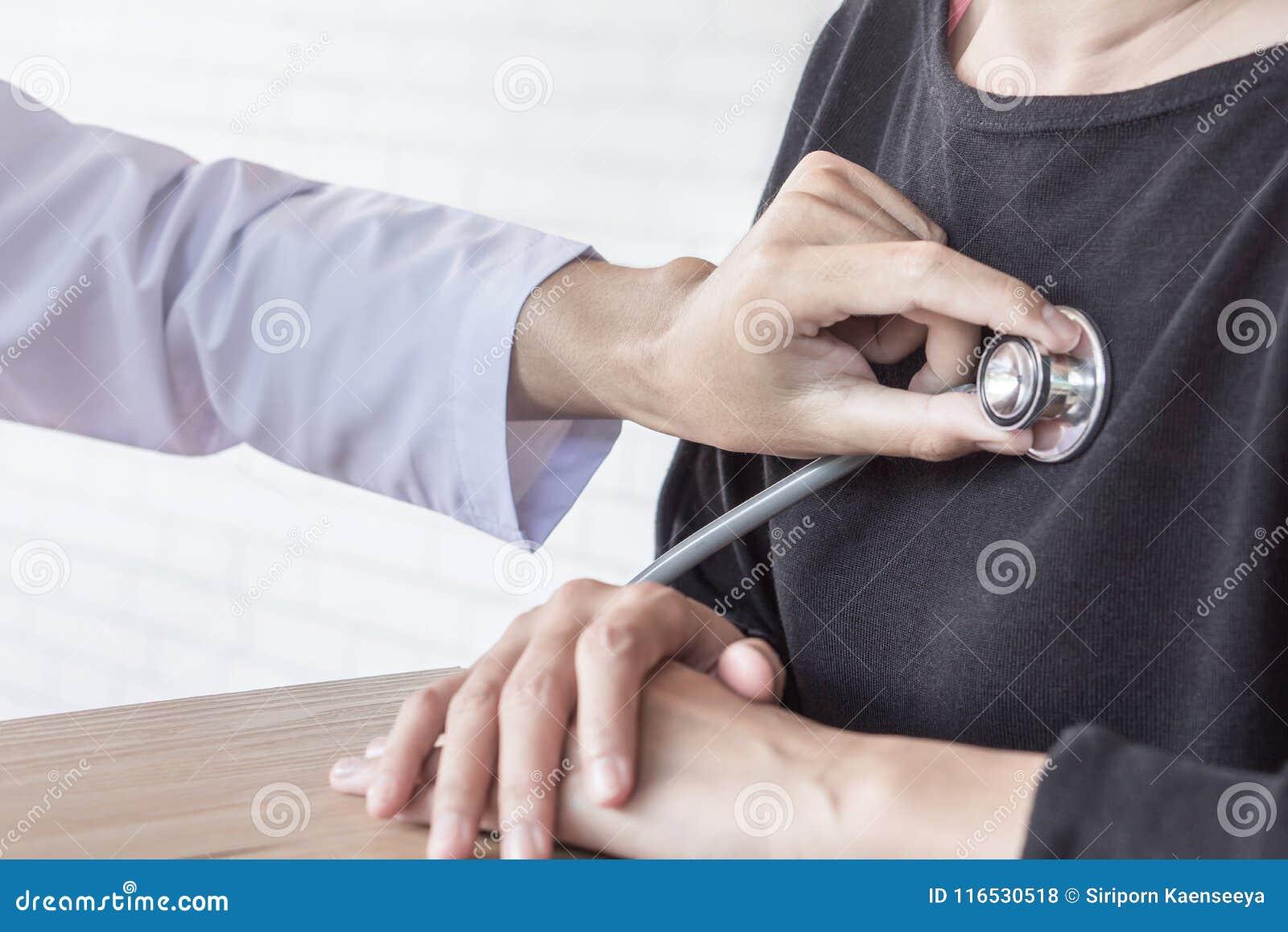 Doutor com estetoscópio à disposição que examina o batimento cardíaco paciente fêmea
