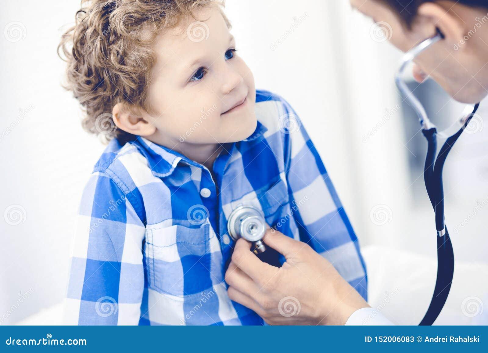 Doutor e crian?a paciente Rapaz pequeno de exame do m?dico Visita m?dica regular na cl?nica Medicina e cuidados m?dicos
