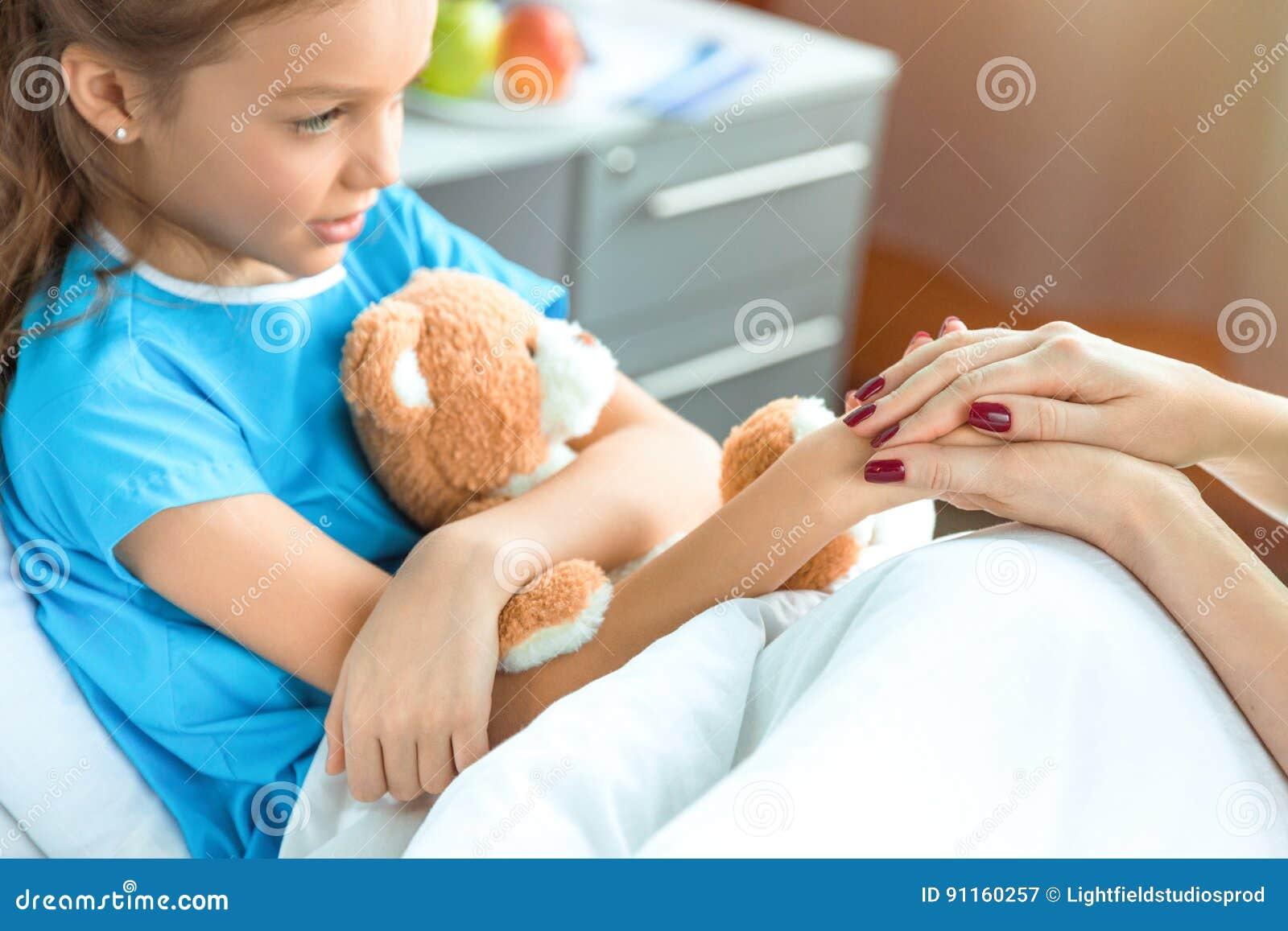 Doutor e paciente pequeno com o urso de peluche que guarda as mãos no hospital