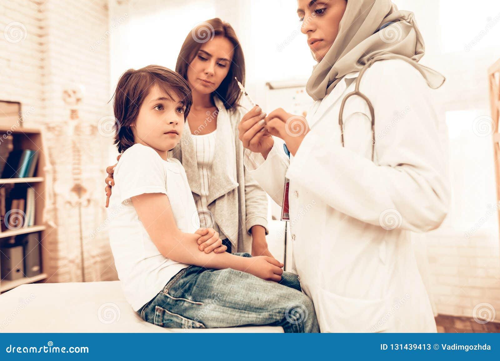 Doutor fêmea árabe Hold Syringe com injeção