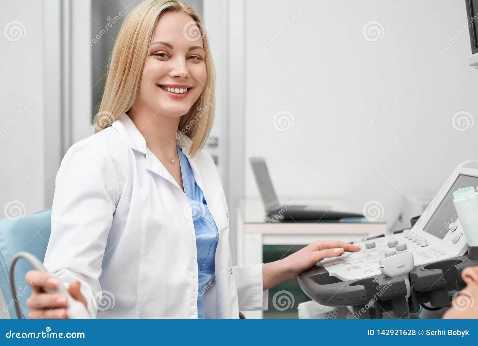 Doutor fêmea bonito que levanta ao fazer a ecografia