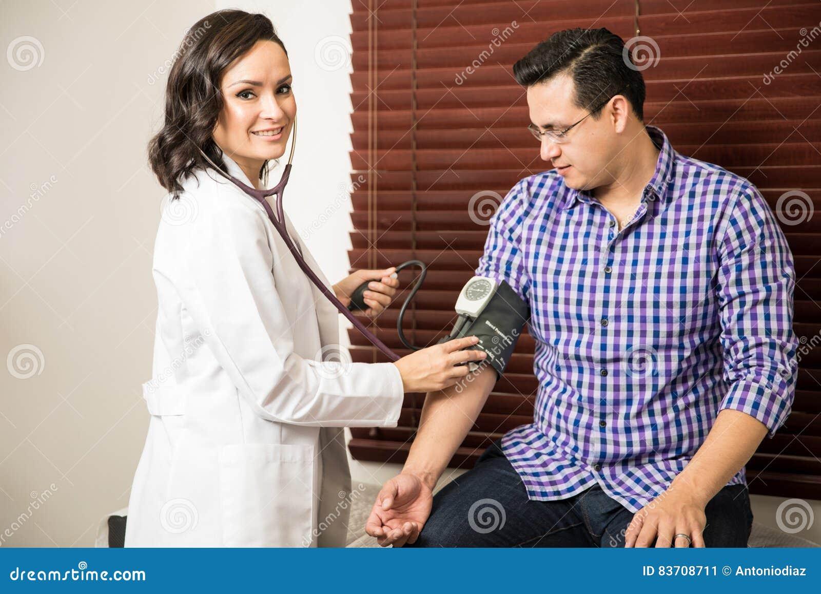 Doutor fêmea bonito que trabalha com paciente