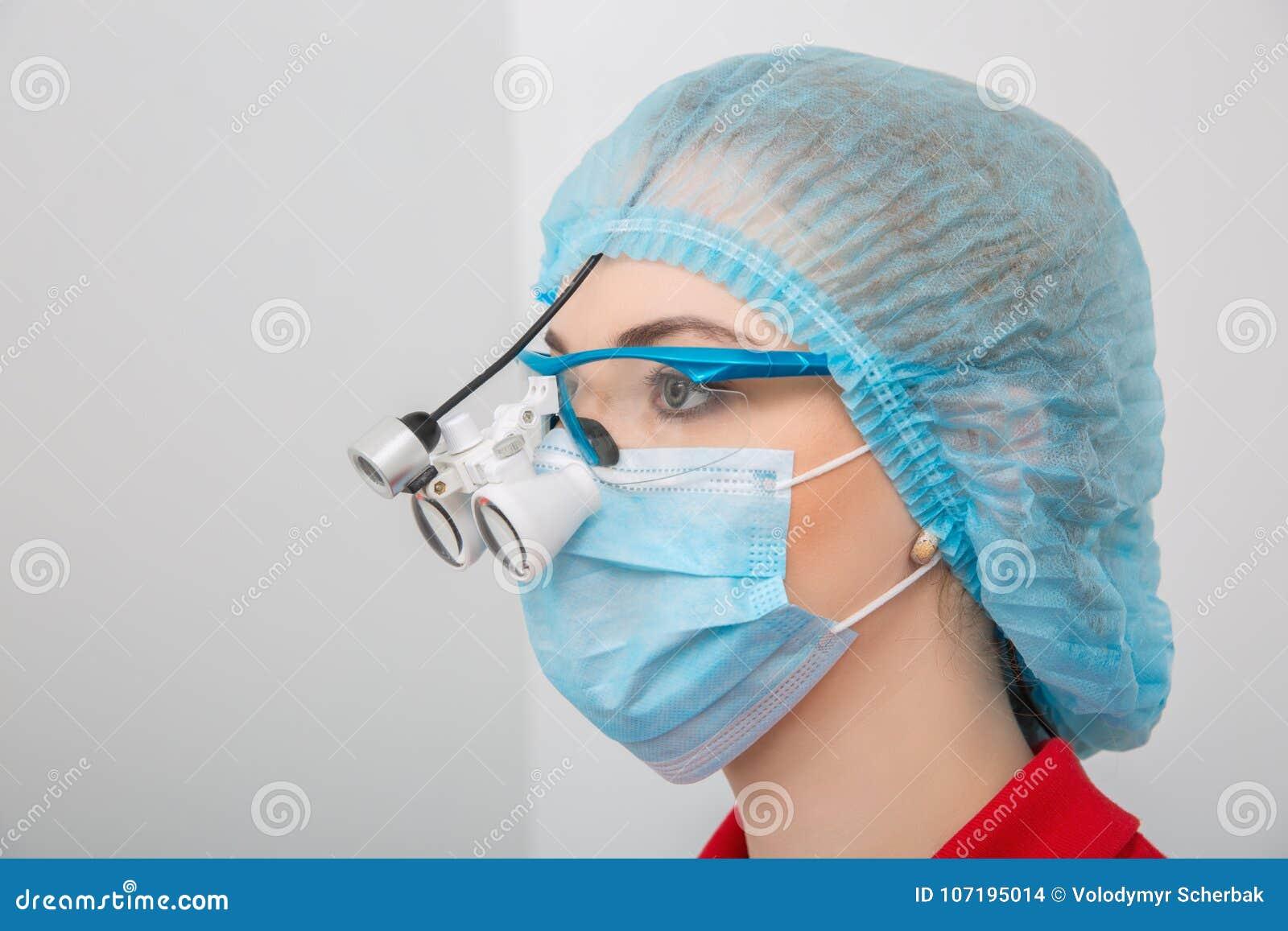 Doutor fêmea novo que veste os binóculos dentais da lupa, retrato do headshot no processo do trabalho