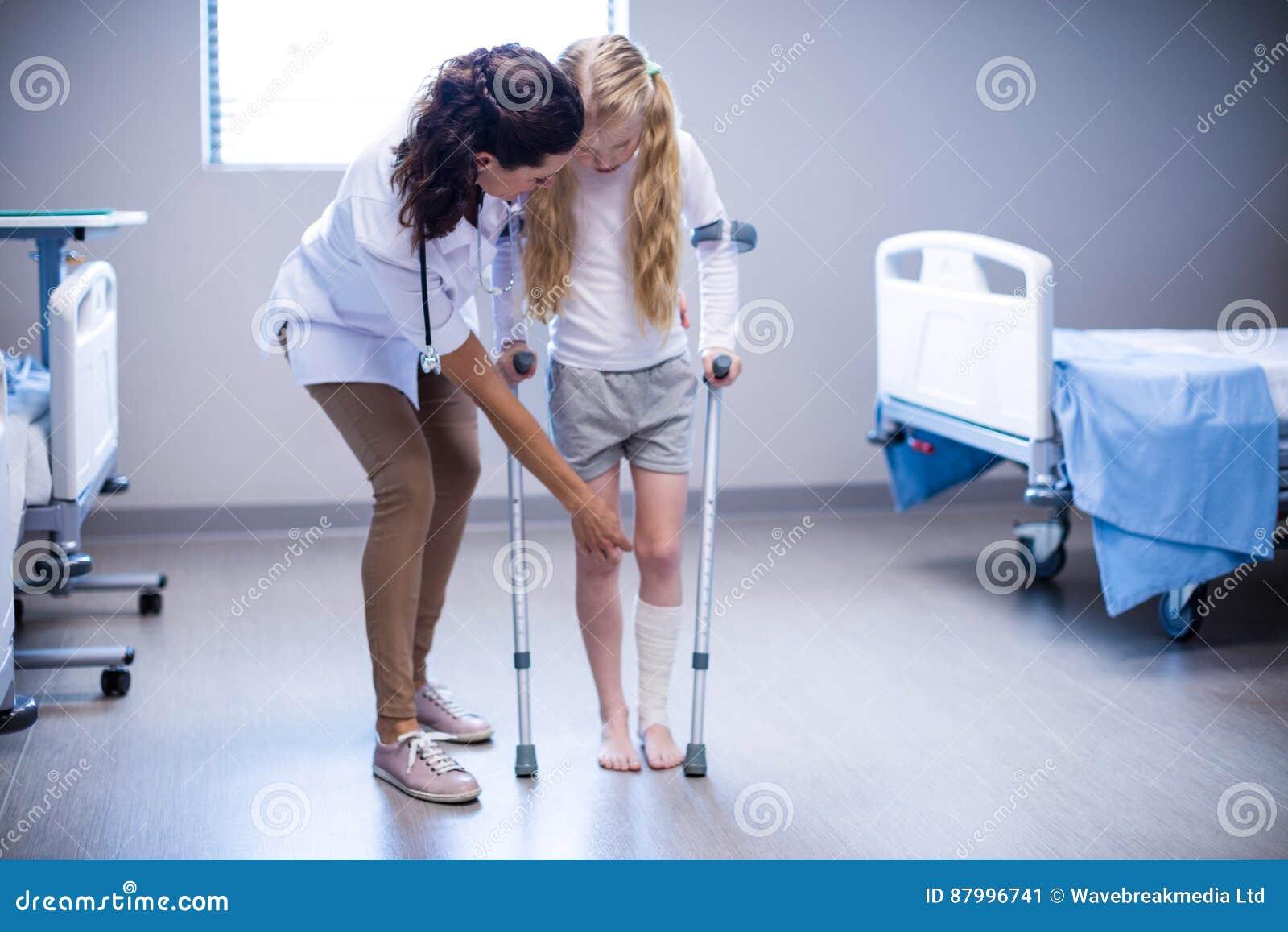 Doutor fêmea que ajuda à menina a andar com as muletas na divisão
