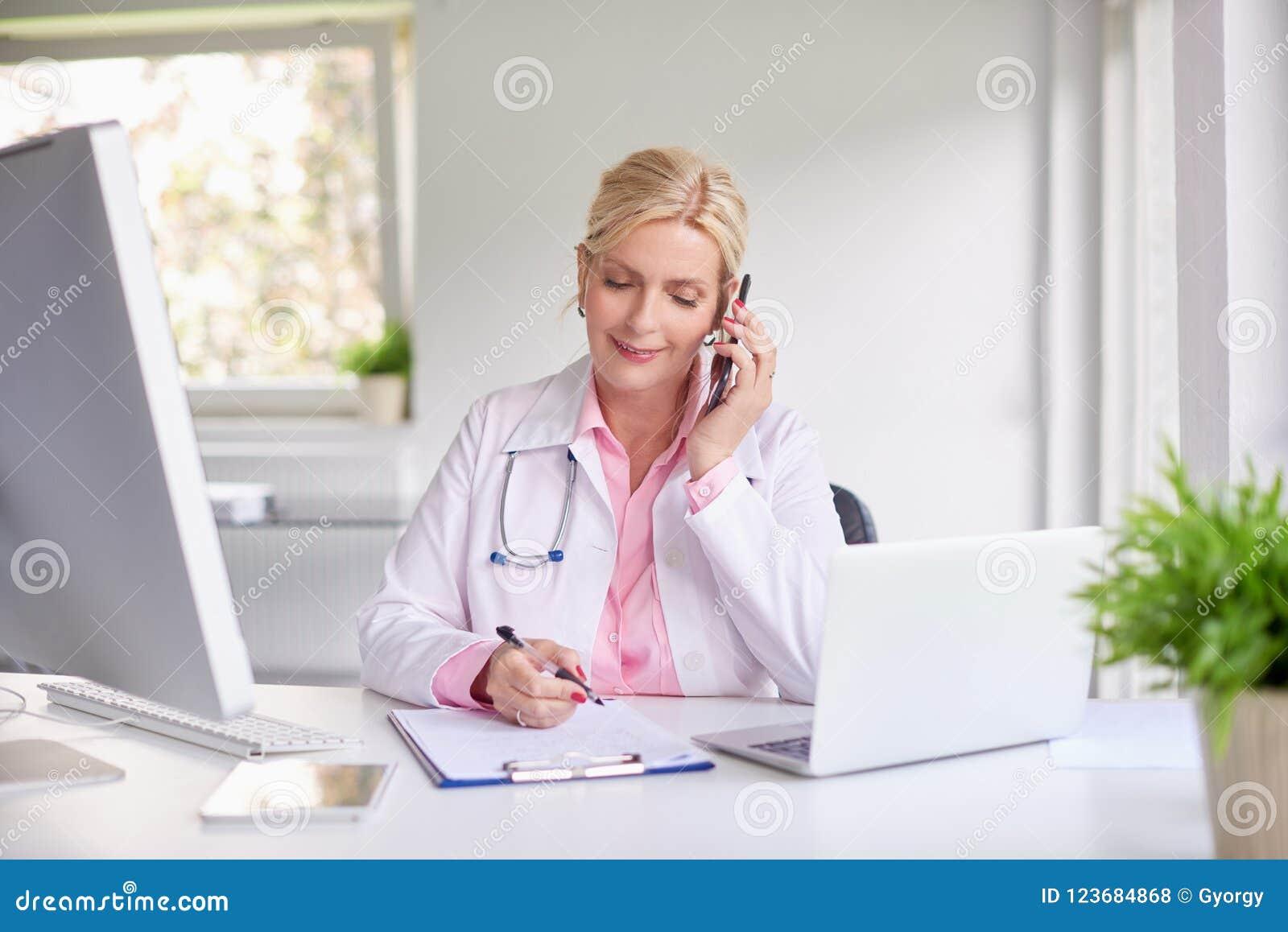 Doutor fêmea que consulta com seu paciente no telefone celular