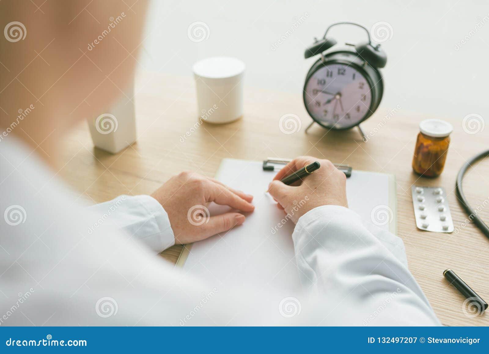 Doutor fêmea que escreve notas no papel da prancheta durante ex médico