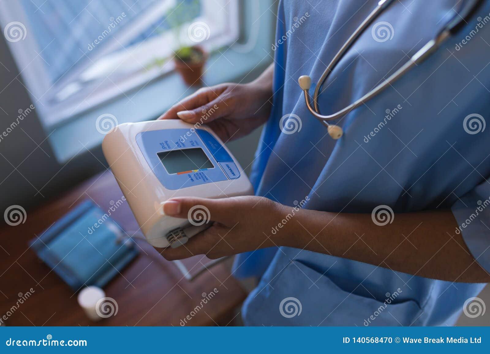 Doutor fêmea que guarda o monitor da pressão sanguínea em casa