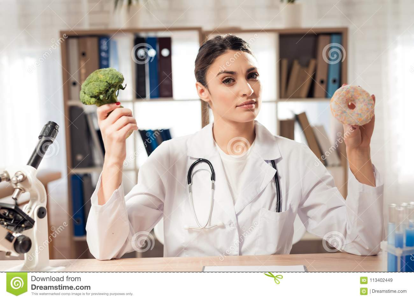Doutor fêmea que senta-se na mesa no escritório com microscópio e estetoscópio A mulher está guardando brócolis e filhós