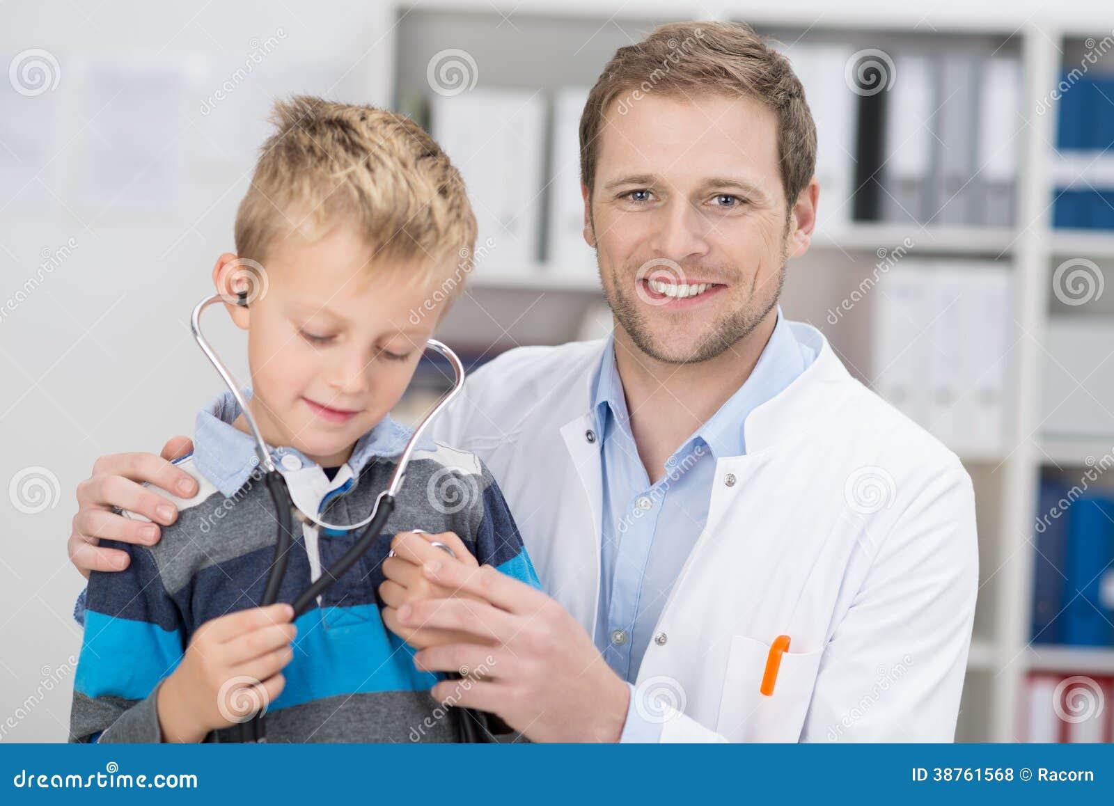 Doutor masculino amigável que examina um menino novo