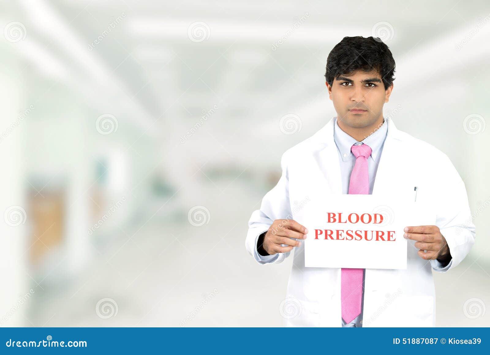 Doutor masculino com o sinal da pressão sanguínea que está no corredor do hospital