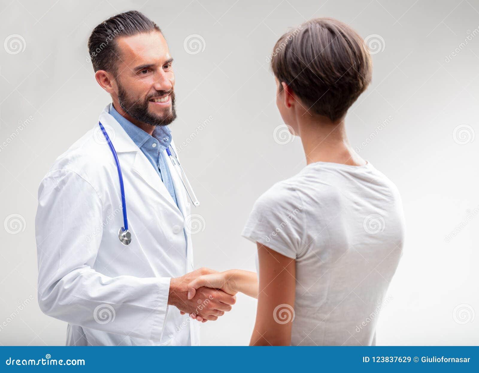 Doutor masculino de sorriso que agita as mãos com um paciente