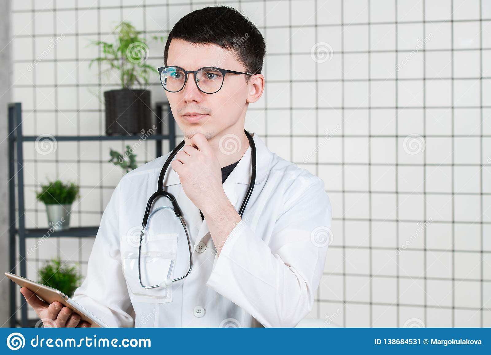 Doutor masculino novo considerável pensativo que usa o tablet pc Tecnologias no conceito da medicina